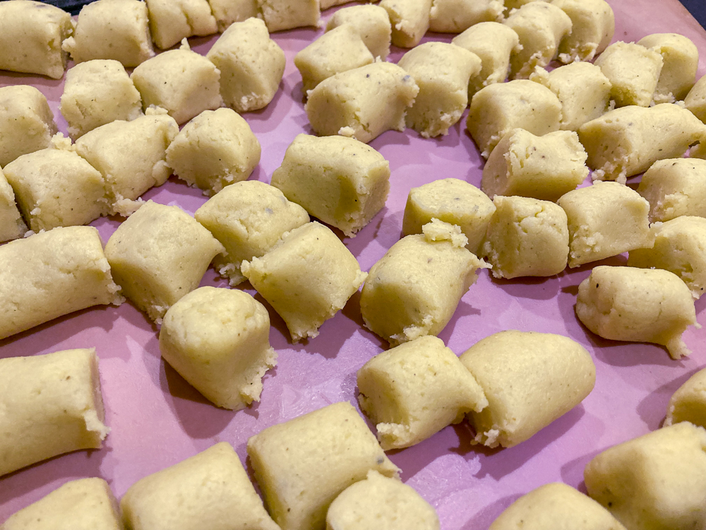 Gnocchi dough cut into pieces resting on a pink baking sheet