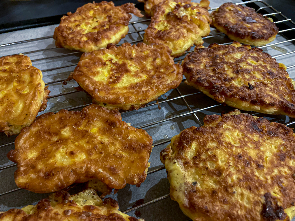 Corn fritters from the book In Praise of Veg resting on a wire rack