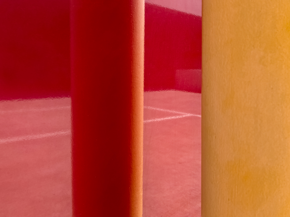Red reflections of a car park next to a yellow bollard