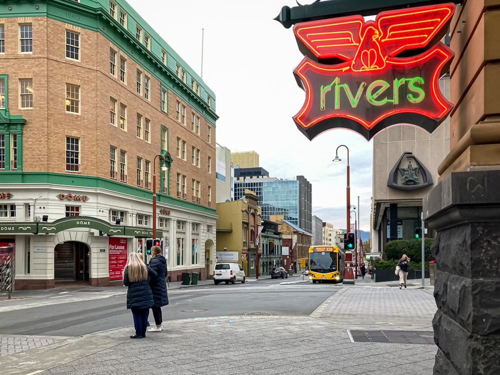The corner of Collins Street and the Hobart Bus Mall, from just behind the Rvers store's neon sign.Two people are waiting to cross Collins Street