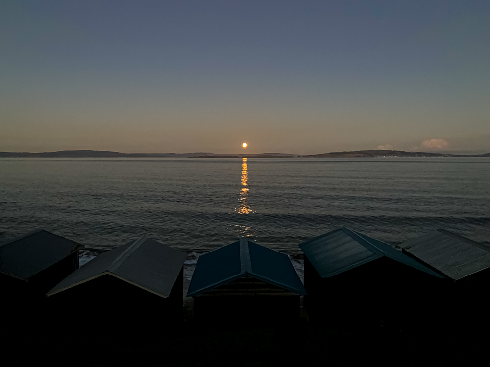 A full moon rising over a series of beach huts
