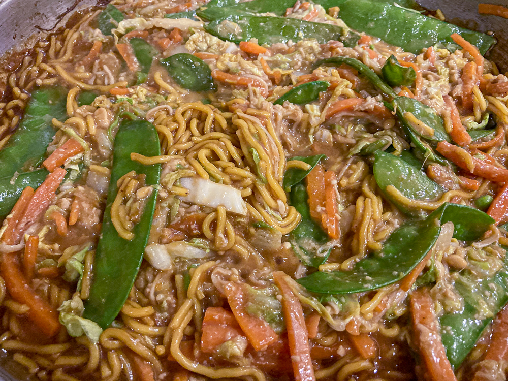 A dish of noodles with snow peas, carrots and other vegetables