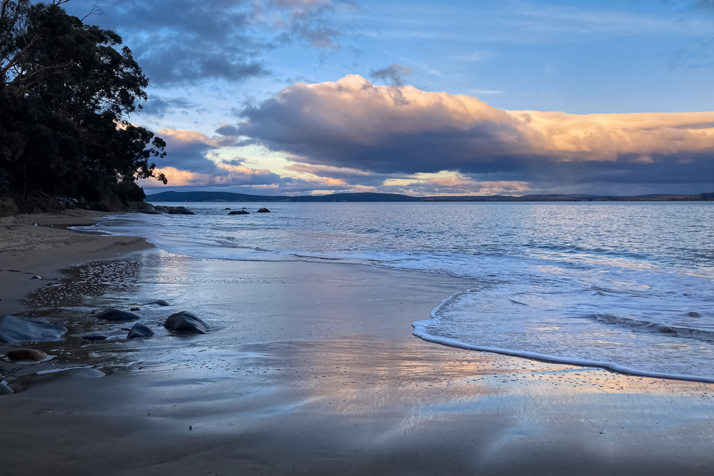 Reflections of the fading light on the wet sand on a beach