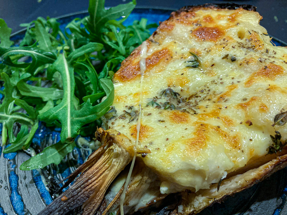 Baked celeriac topped with cheese and served with rocket leaves