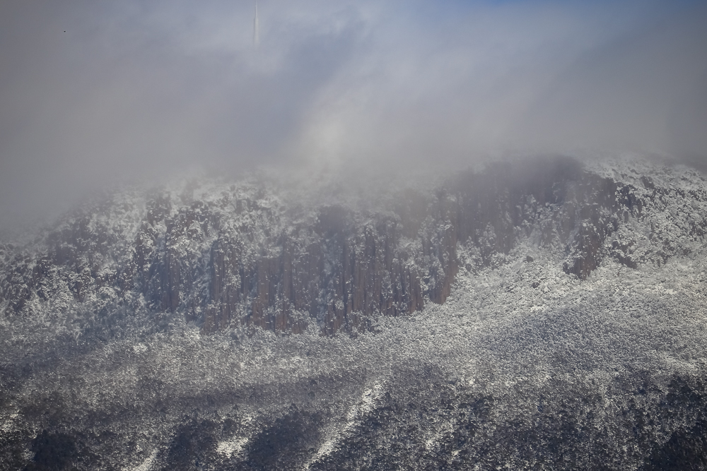 A close-up photo of kunanyi covered in snow and low cloud