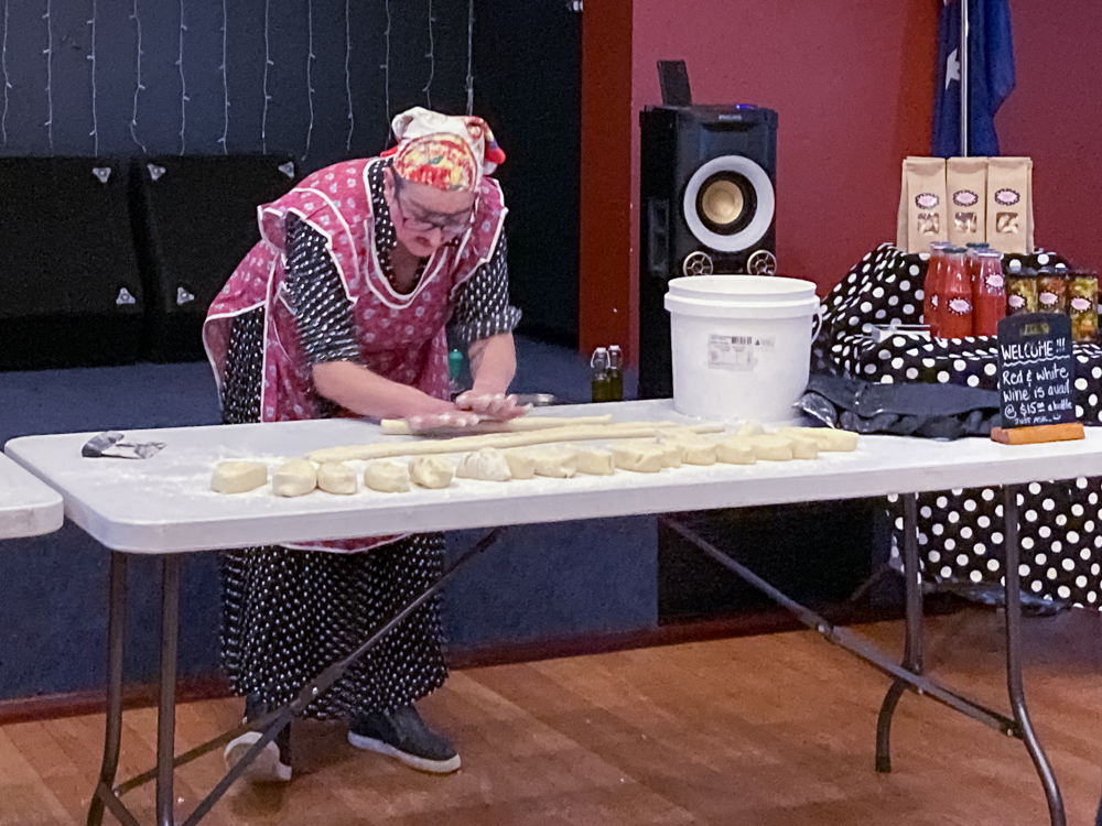 An Italian lady in a red apron and head scarf making gnocchi