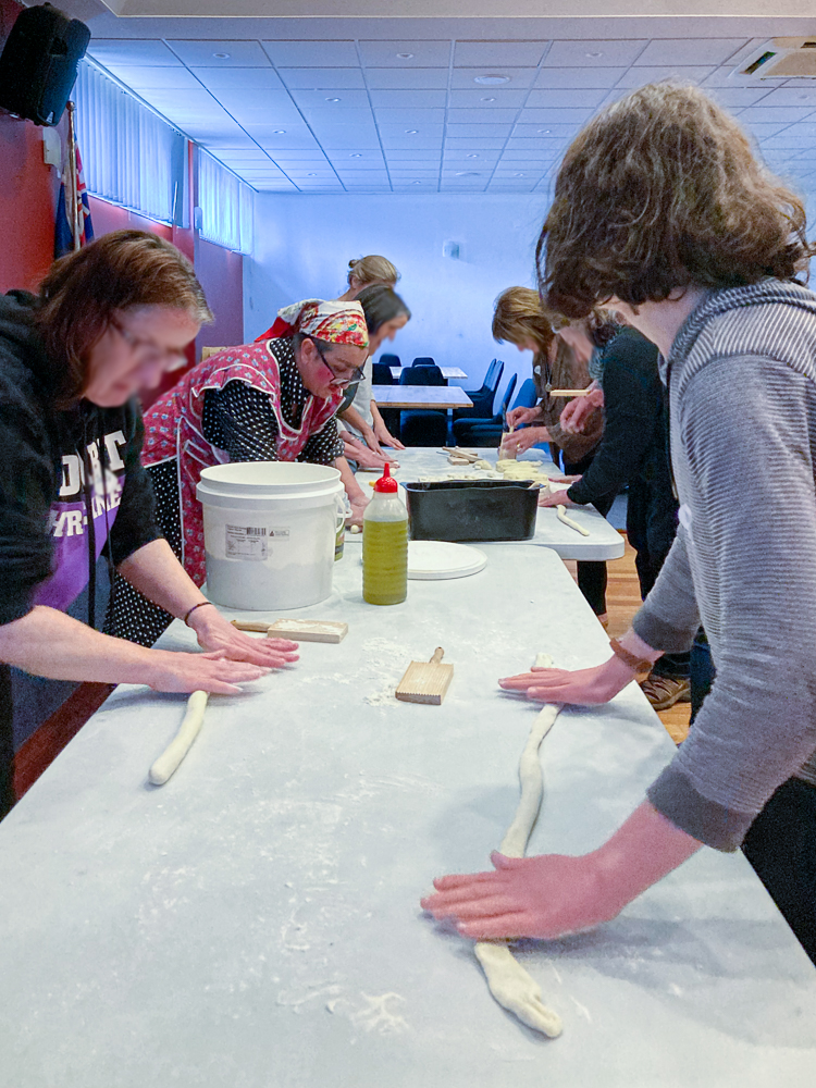 People at a table rolling strands of gnocchi dough